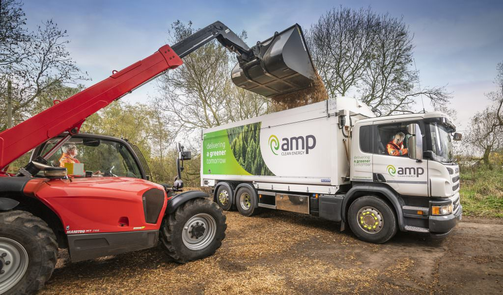Tipper loading an Amp lorry with wood chip