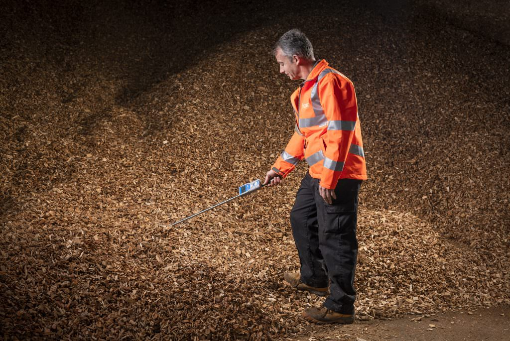 Workman checking wood chip quality
